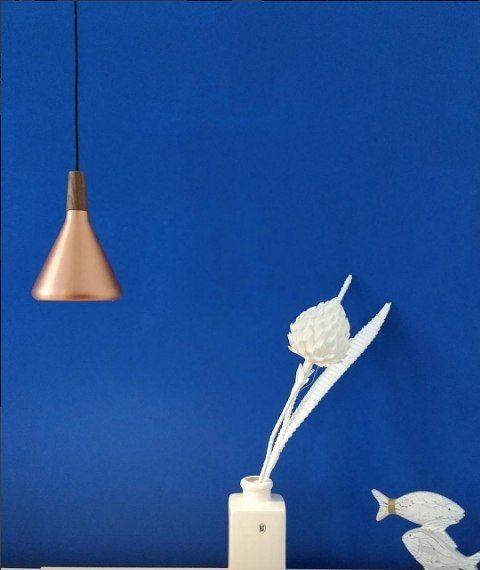 miedziana lampa wisząca do niebieskiej ściany nad stolik