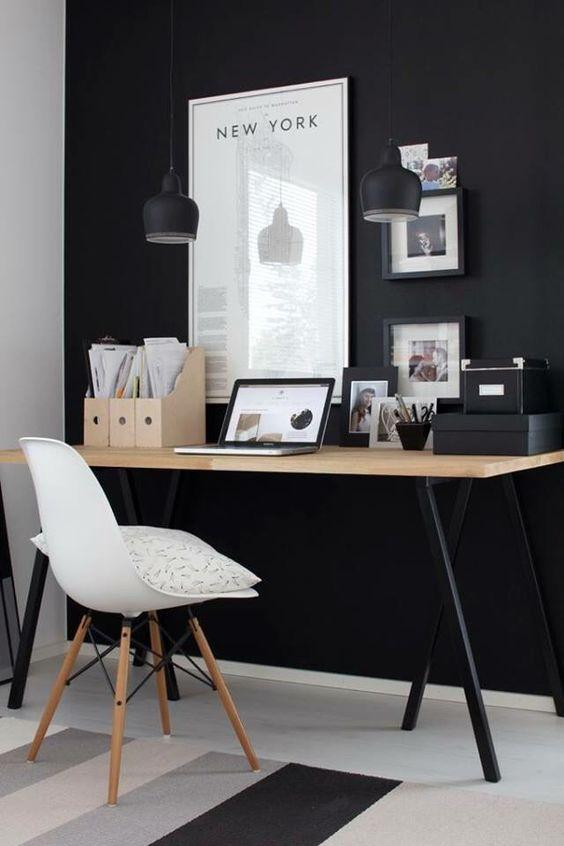dwie małe czarne lampy wiszące nad drewniany stół i do czarnej ściany