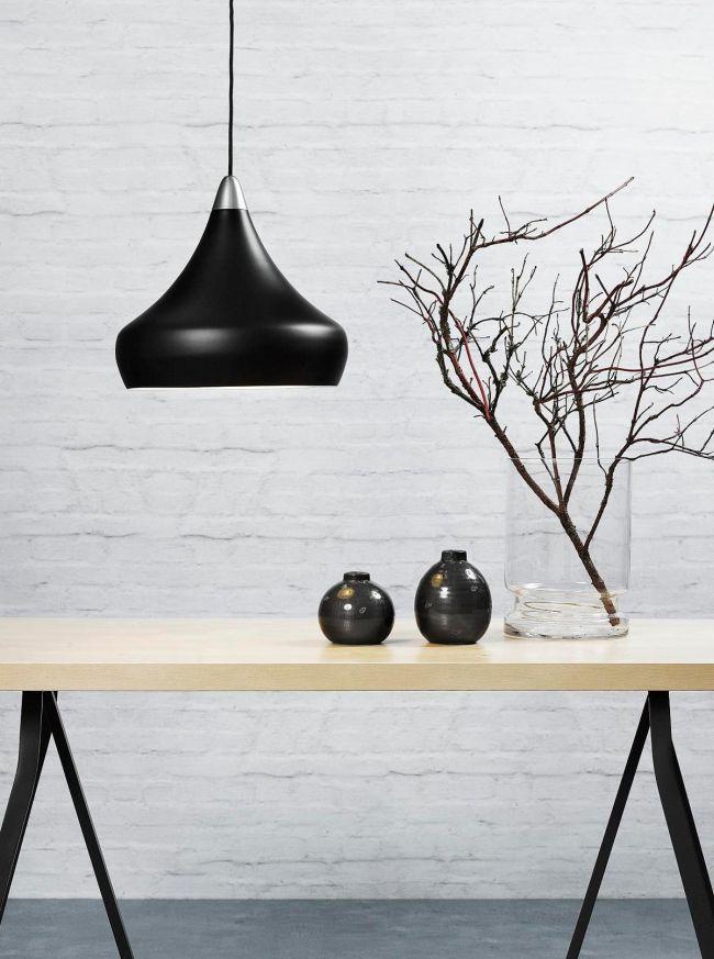 czarna lampa wiszaca nad jasny stół drewniany i do białej ściany