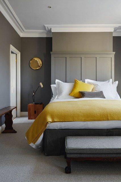 szara sypialnia z żółtym łóżkiem