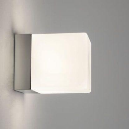 kwadratowy, minimalistyczny, nowoczesny kinkiet z białym kloszem na srebrnej podstawie