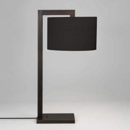 czarna lampa stołowa z ostrymi, geometrycznymi kształtami i okrągłym abażurem z materiału