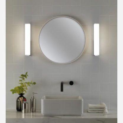 podłużny kinkiet z jasnym, wyraźnym światłem, mleczny klosz i srebrna podstawa, nowoczesne oświetlenie łazienki