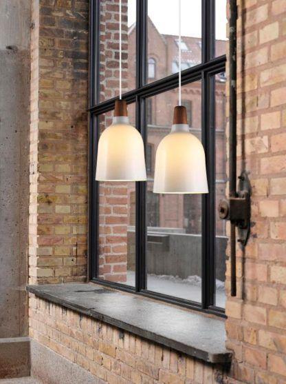 skandynawska lampa wisząca ze szklanym kloszem i drewnianymi detalami - aranżacja czerwona cegła