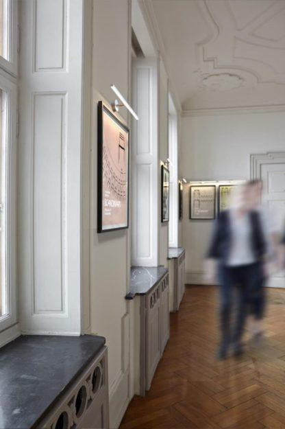 biały, nowoczesny, podłużny kinkiet do oświetlenia dzieł sztuki