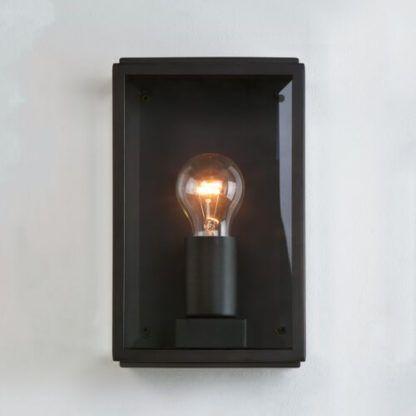 czarny kinkiet z przezroczystymi, szklanymi ściankami odsłaniającymi żarówke