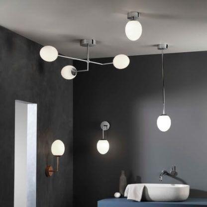 lampy na cienkiej, smukłej podstawie z kloszami z mlecznego szkła w kształcie kuli