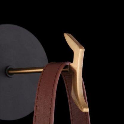 czarny, metalowy kinkiet z brązowym paskiem skórzanym