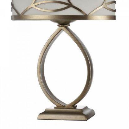 złota lampa stołowa z owalnym, białym abazurem ze złotymi dekorami