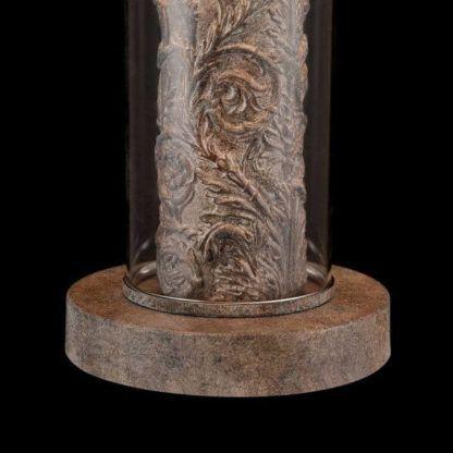 lampa stołowa z metalową, mocno, klasycznie zdobioną podstawą zamkniętą w szklanej, przezroczystej obudowie