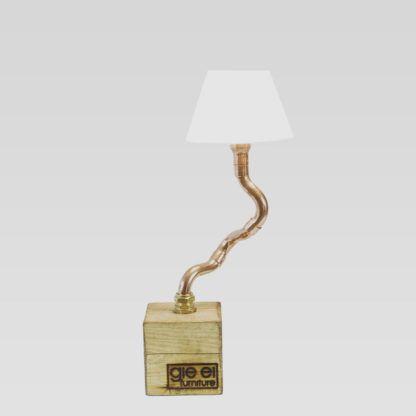 miedziana lampa stołowa na drewnianej podstawie