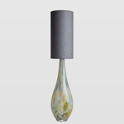 szklana lampa stołowa z szarym abażurem, odcienie beże i zieleni