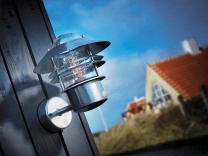 srebrny, metalowy kinkiet ze szklanym kloszem, wbudowany czujnik ruchu