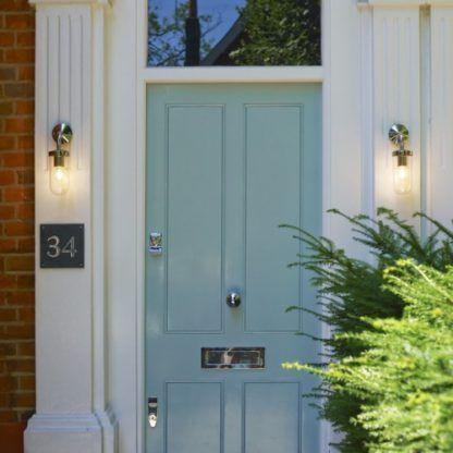 srebrny kinkiet ze szklanym kloszem,skierowanym w dół - aranżacja oświetlenie drzwi wejściowych
