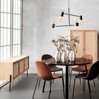 czarna lampa wisząca nad stołem z welurowymi krzesłami