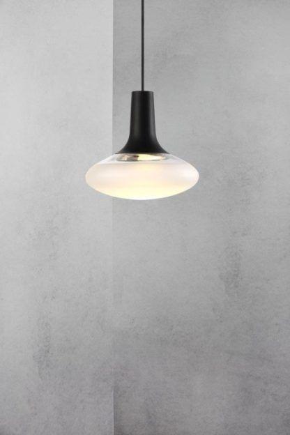 owalna szklana lampa na szarej ścianie