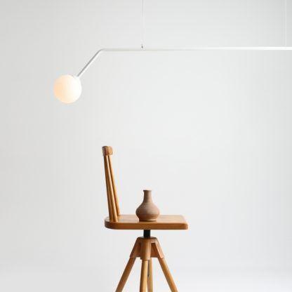 długa biała lampa wisząca nad stół