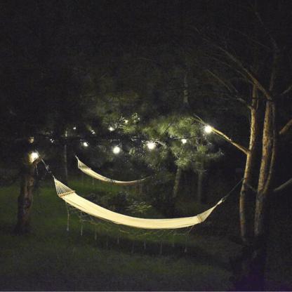 girlandy do ogrodu - nastrojowe oświetlenie drzew i hamaka