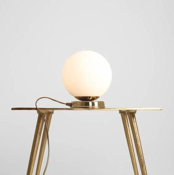 złota lampa stołowa ze szklanym kloszem