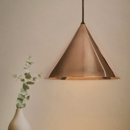 złota lampa wisząca do beżowej ściany