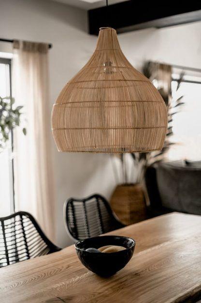 duża rattanowa lampa nad drewniany stół