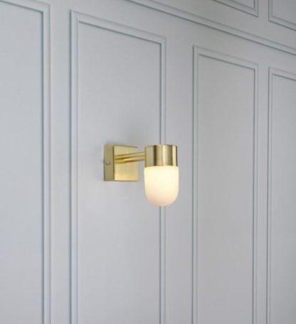 złoty kinkiet na szarej ścianie z dekorami