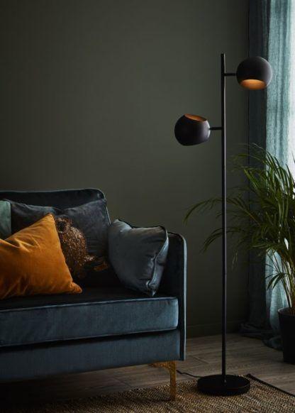 czarna lampa podłogowa w zielonym salonie