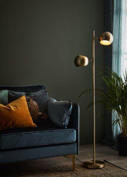 złota lampa podłogowa w zielonym salonie