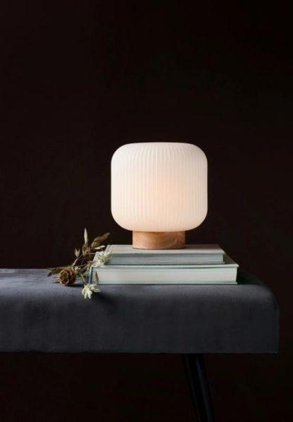 szklana lampa stołowa na drewnianej podstawie