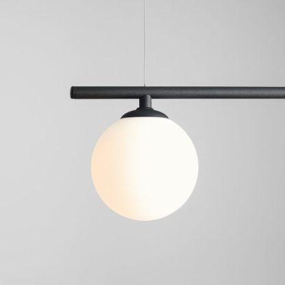 czarna lampa wisząca z białą kulą ze szkła