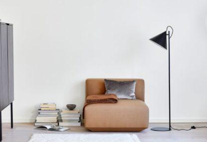 czarna lampa podłogowa z pomarańczową kanapą