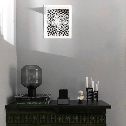 szklana lampa stołowa na szarej ścianie