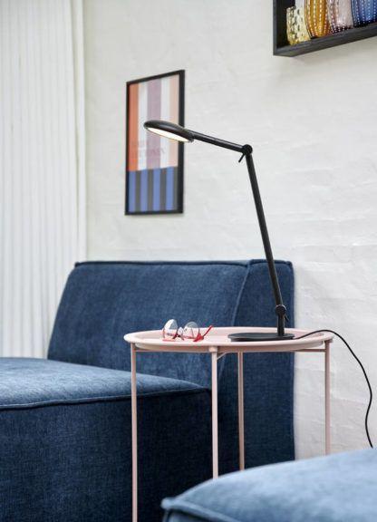 czarna lampa biurkowa przy granatowej sofie