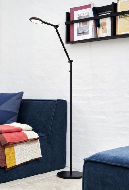 czarna lampa podłogowa z granatową sofą w salonie