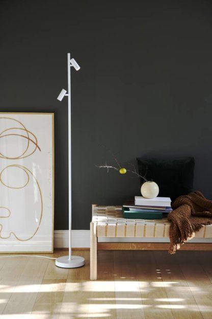 biała lampa podłogowa na grafitowej ścianie