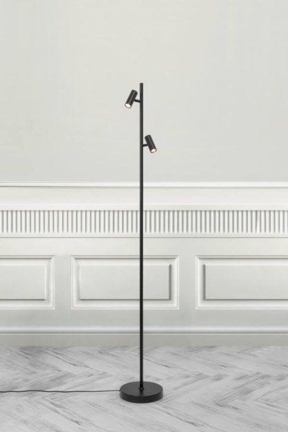 czarna lampa podłogowa na szarej ścianie