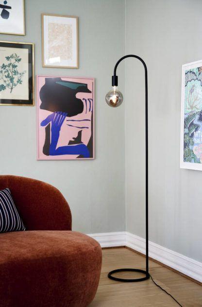 czarna lampa podłogowa obok bordowej kanapy