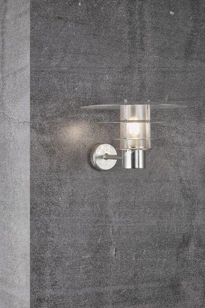 srebrny kinkiet na betonowej ścianie