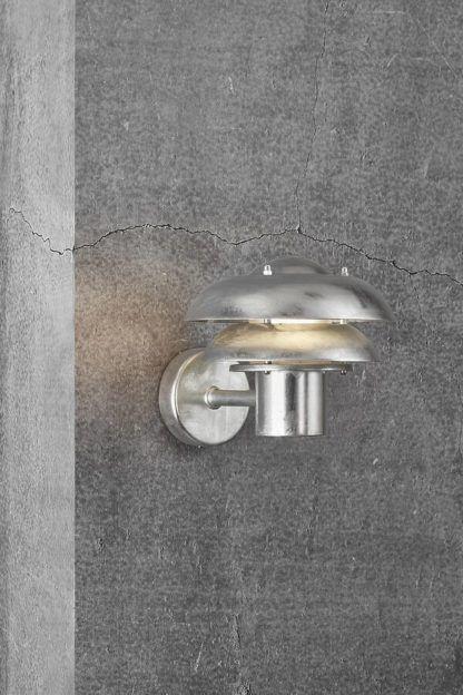 srebrny kinkiet na szarą elewację