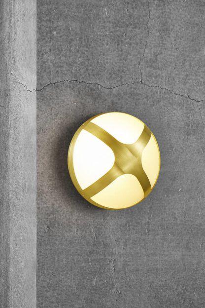okrągła złota lampa elewacyjna na betonie