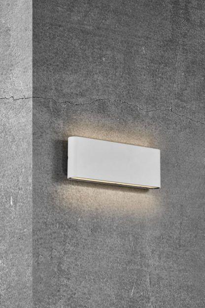 podłużny biały kinkiet na betonowej ścianie