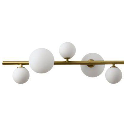 złota podłużna lampa wisząca nad stół