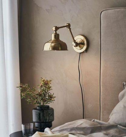 złoty kinkiet w szarej sypialni