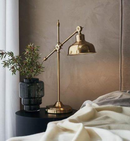 złota lampa nocna w szarej sypialni