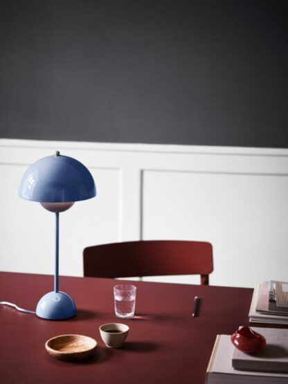 niebieska lampa stołowa na bordowym stole