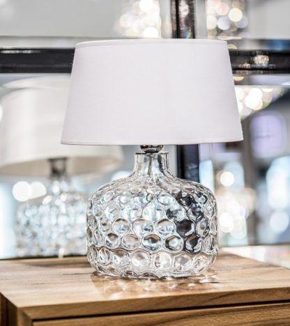 niska lampa stołowa z białym abażurem i transparentną podstawą w tłoczone koła