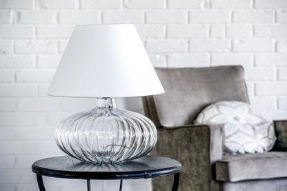lampa stołowa w stylu modern classic. bezbarwna podstawa w kształcie spłaszczonej kuli, biały abażur