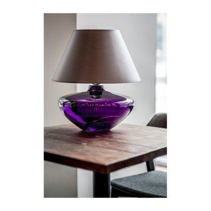 elegancka lampa stołowa ze szklaną podstawą w fioletowym kolorze i beżowym abażurem