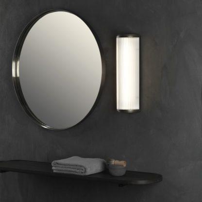 pionowy kinkiet z mlecznym kloszem i ciemną podstawą -aranżacja łazienka