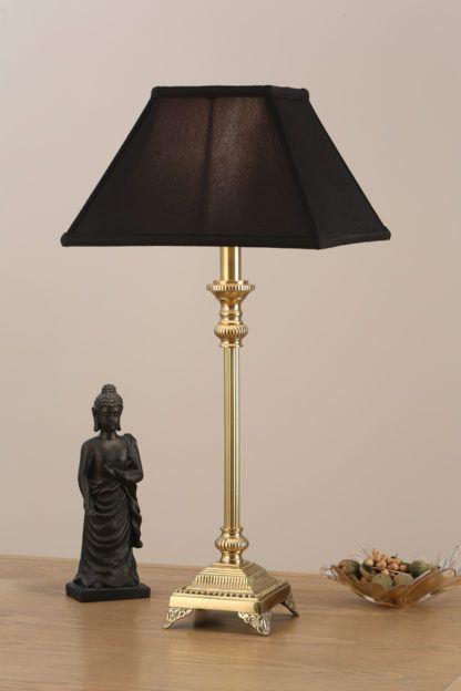 złota lampa podłogowa ze zdobioną podstawą i ciemnym abażurem